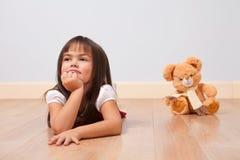 Menina bonito em um assoalho de madeira Fotografia de Stock Royalty Free