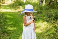 Menina bonito em um chapéu com um telefone em uma floresta do verão Fotos de Stock Royalty Free