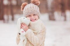 Menina bonito em um chapéu com uma lebre macia favorita do brinquedo Fotos de Stock