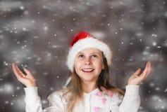 A menina bonito em um chapéu do Natal aprecia a neve de queda Imagens de Stock Royalty Free