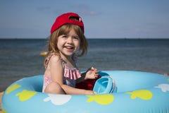 Menina bonito em um tampão vermelho que joga na praia contra o mar azul Fotos de Stock Royalty Free