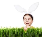 Menina bonito em um traje do coelho que espreita fora da grama Fotografia de Stock Royalty Free