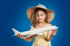 A menina bonito em um vestido amarelo realiza nas mãos um avião do brinquedo Imagem de Stock Royalty Free