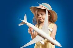A menina bonito em um vestido amarelo realiza nas mãos um avião do brinquedo Imagens de Stock