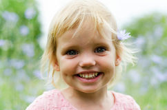 Menina bonito em um vestido cor-de-rosa que sorri no parque Foto de Stock Royalty Free