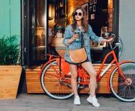 A menina bonito em um vestido do verão, em um revestimento da sarja de Nimes, em uns óculos de sol e em um saco está com a bicicl Imagens de Stock