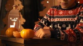 A menina bonito em uma camiseta de ano novo escreve um desejo de ano novo a Santa Claus no movimento lento vídeos de arquivo