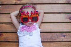 Menina bonito em vidros vermelhos do feliz aniversario Fotografia de Stock Royalty Free