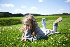 A menina bonito encontra-se na grama verde Imagens de Stock