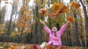 A menina bonito engraçada, alegre salta jogando acima outono amarelo um movimento lento caído das folhas video estoque