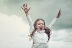 Menina bonito excitada que aumenta os braços e que grita, conceito da felicidade imagens de stock