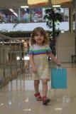 A menina bonito está andando ao longo de um supermercado com um pacote da cor Fotografia de Stock Royalty Free