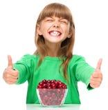 A menina bonito está comendo as cerejas que mostram o polegar acima do suspiro imagem de stock royalty free