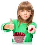 A menina bonito está comendo as cerejas que mostram o polegar acima do suspiro fotos de stock