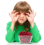 A menina bonito está comendo cerejas fotografia de stock royalty free