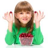 A menina bonito está comendo cerejas imagens de stock royalty free