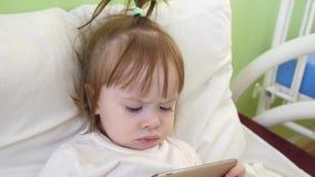 A menina bonito está encontrando-se na cama no hospital de crianças, olhando desenhos animados engraçados no smartphone vídeos de arquivo