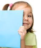 A menina bonito está escondendo atrás de um livro Fotografia de Stock Royalty Free