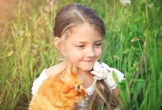 A menina bonito está guardando um gato vermelho que senta-se na grama imagens de stock