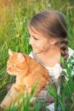 A menina bonito está guardando um gato vermelho que senta-se na grama fotos de stock