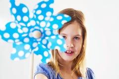 A menina bonito está guardando um moinho de vento, mostrando à câmera imagens de stock royalty free