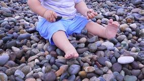 A menina bonito está jogando com cubeta em uma praia, recolhendo rochas Imagem de Stock