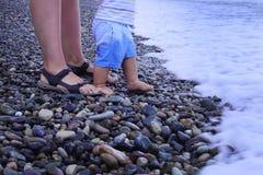 A menina bonito está jogando com cubeta em uma praia, recolhendo rochas Fotos de Stock Royalty Free