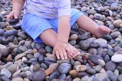 A menina bonito está jogando com cubeta em uma praia, recolhendo rochas Fotos de Stock