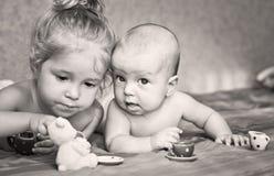 A menina bonito está jogando com seu irmão mais novo Imagens de Stock