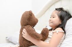A menina bonito está jogando com um urso de peluche imagens de stock royalty free