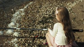 A menina bonito está jogando com uma vara de pesca em um barco de pesca perto do rio vídeos de arquivo