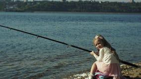 A menina bonito está jogando com uma vara de pesca em um barco de pesca perto do rio video estoque