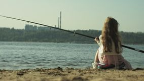 A menina bonito está jogando com uma vara de pesca em um barco de pesca perto do rio filme