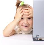 A menina bonito está olhando para fora de seu portátil fotos de stock royalty free