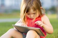 A menina bonito está sentando-se com uma tabuleta na grama no parque Retrato emocional Imagem de Stock Royalty Free
