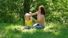 A menina bonito está sorrindo quando a mãe nova bonita pentear seu cabelo que se senta na grama verde no parque mom filme