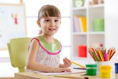 A menina bonito está tirando com os lápis no pré-escolar imagem de stock