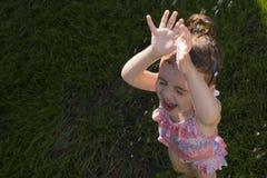 A menina bonito está tomando um chuveiro exterior com expressão na cara Imagem de Stock