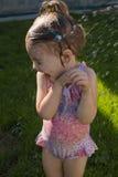 A menina bonito está tomando um chuveiro exterior com expressão na cara Fotos de Stock Royalty Free