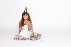 A menina bonito está sentando-se no fundo branco Imagem de Stock