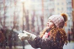 A menina bonito estica sua mão para travar flocos de neve de queda Foto de Stock Royalty Free