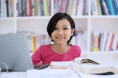 A menina bonito estuda com o portátil na biblioteca foto de stock