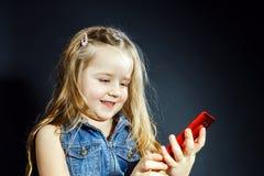 A menina bonito fala usando o telefone celular novo imagem de stock