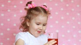 A menina bonito feliz bebe o batido da framboesa e sorri Bebida do vegetariano Retrato do close-up de uma criança que aprecie a filme