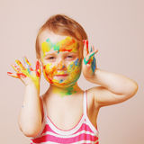 Menina bonito feliz com mãos pintadas coloridas Fotografia de Stock