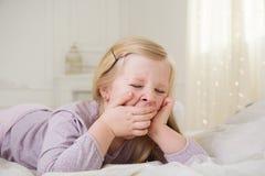 Menina bonito feliz da criança que boceja na cama Fotografia de Stock