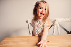 Menina bonito feliz da criança que joga em casa na cozinha Imagens de Stock Royalty Free