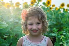 Menina bonito feliz entre girassóis Imagem de Stock Royalty Free