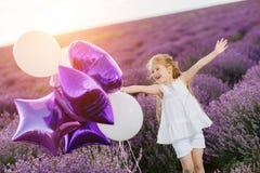 Menina bonito feliz no campo da alfazema com balões roxos Conceito da liberdade fotos de stock royalty free