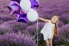 Menina bonito feliz no campo da alfazema com balões roxos Conceito da liberdade fotos de stock